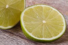Cutting in half a fresh lime on a background of the old wooden Royalty Free Stock Images