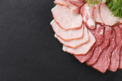 Cutting ham with vegetables assortment on black background stock image