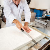 Cutting of hand-made nougat made of Italian white dough Royalty Free Stock Photography