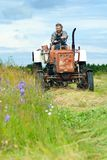 Cutting hay on tractor. A man operates an old red tractor, cutting up hay in a field. The field is full of wild flowers Stock Photo