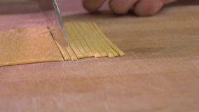 Cutting homemade pasta with a knife. Amateur cooking at home. 4K steadicam closeup shot stock video
