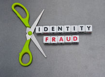 Cutting identity fraud. Pair scissors against text  identity fraud  in uppercase letters inscribed on small white cubes , gray background Stock Photography