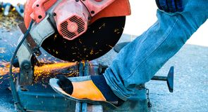 Cutting iron steel rods. A worker cutting iron steel rods using a power metal cutter Royalty Free Stock Photos