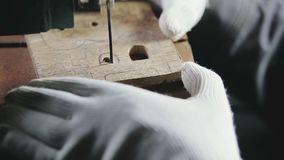Cutting jigsaw in a wooden workpiece, the symbol of bitcoin. Hands in white gloves jigsaw to cut a wooden workpiece, the symbol of bitcoin stock footage