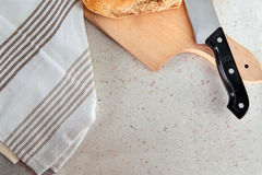 Cutting kitchen board, bread, fabric and knife on marble table Stock Images