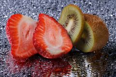 Cutting kiwi and strawberries with water drops Stock Image