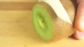 Cutting kiwi with white knife on wooden cutting board stock video footage