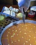 Cutting Kunfa or Kinafa, Arabic Sweets with Cheese for Ramadan a. Cutting Kunfa or Kinafa, Arabic Sweets with Cheese, Nuts and Other Ingredients for Ramadan and Royalty Free Stock Images