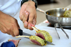 Cutting lamb rack or chop. Hand of chef Cutting lamb rack or chop royalty free stock images