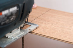 Cutting a laminated floor board Royalty Free Stock Photo