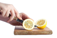 Cutting a lemon isolated on white background Stock Images