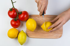 Cutting Lemons and Tomatoes on Wooden Cutting Board Royalty Free Stock Photography