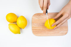 Cutting Lemons on Wooden Cutting Board Royalty Free Stock Photography