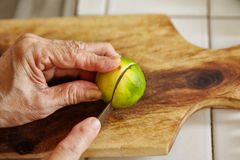Cutting lime. On the wooden cutting board Stock Photography