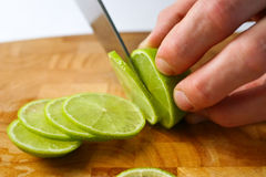Cutting limes. Slicing limes on a wooden chopping board Stock Photos