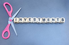 Cutting or liquidating investments. Text ' investments ' in black uppercase letters inscribed on white cubes with a pair of scissors with purple handles arranged Royalty Free Stock Photo