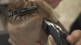 Cutting little boy with electrical shaver in children hairdressing salon. Children hairdresser doing boy hairstyle with. Electric razor in barber shop close up stock video