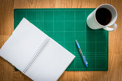 Cutting mats , notebook , pen , cup of coffee on the wood backgr. Green Cutting mats  , notebook , pen , cup of coffee on the wood background Royalty Free Stock Photography