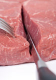 Cutting meat. A macro shot of a someone cutting thru a slab of raw meat Stock Photography