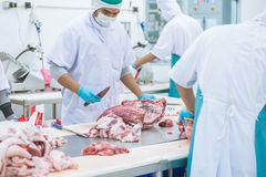 Cutting meat slaughterhouse workers in the factory Stock Photos