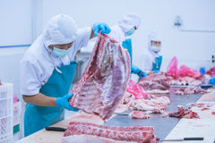 Cutting meat slaughterhouse workers in the factory. Cutting meat slaughterhouse workers in the refrigerator Stock Photography