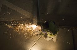 Cutting metal. A man cutting a steel pole Royalty Free Stock Image