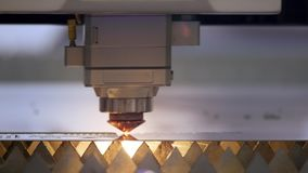 Cutting of metal. Sparks fly from laser. Industrial laser cutter with sparks. The programmed robot head cuts with the