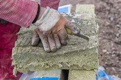 Cutting mineral wool panel with a craft knive. At construction site. Selective focus Stock Photo