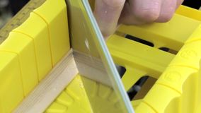 Cutting mitered cuts using saw and mitre box stock footage