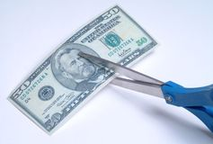 Cutting Money 1. A fifty dollar bill being cut by a pair of scissors Stock Images