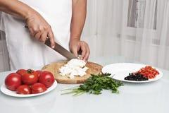 Cutting mozzarella into pieces. Royalty Free Stock Image