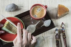 Cutting multi-layered cake called lapis legit or spekkoek, with bamboo napkin and Indonesian souvenir royalty free stock image