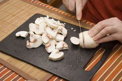 Cutting mushroom. Chef cutting mushroom on black board Stock Images