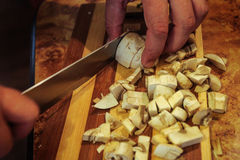 Cutting mushrooms with a knife. Knife mushrooms cooking male hands Royalty Free Stock Photos