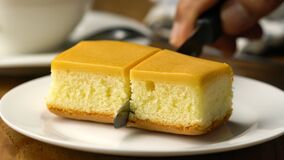 Cutting mustard cake into two portions.