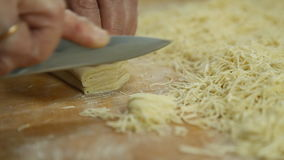 Cutting of noodles roll on cutting board by hands close up stock footage