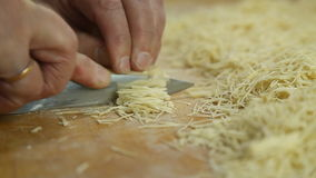 Cutting of noodles roll on cutting board by hands close up stock video footage