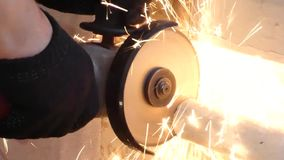 Cutting old metal pipe with angle grinder. Side grinder. Man in black gloves work with power tool, lot of bright sparks flying away. Disassembling of water stock footage