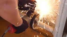 Cutting old metal pipe with angle grinder or side grinder. Man in black gloves work with power tool, lot of bright sparks flying away. Disassembling of water stock footage