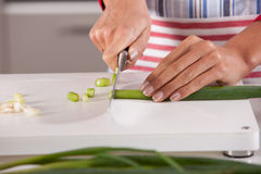 Cutting the onions. Woman hands cutting the spring onions with a big knife Royalty Free Stock Image