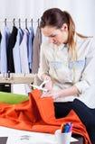 Cutting the orange fabric Stock Photo
