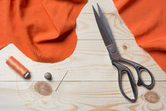 Cutting orange fabric with a taylor scissors on wooden table Royalty Free Stock Photo