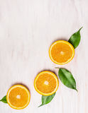 Cutting orange fruits with leaves on white wooden background. With copy space, top view Royalty Free Stock Photo