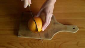 Cutting orange into two halves. Female hands cutting orange into two halves on a wooden table stock video footage