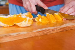 Cutting oranges Royalty Free Stock Photo