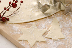 Cutting out Christmas biscuits. Stock Photos