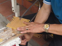 Cutting out by a fret saw. The master cuts a fret saw templates for production of souvenirs Royalty Free Stock Image