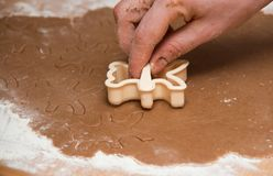 Cutting out  a gingerbread with human hand Stock Photos