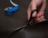 Cutting-out of leather in the atelier. Using blue twisted tape measure and black scissors. Cutting-out of brown leather in the atelier. Using blue twisted tape Royalty Free Stock Photo