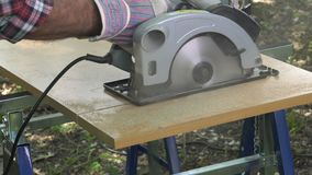 Cutting a panel with a circular saw. Electric saw progress during cutting operation stock video footage